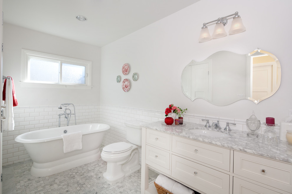 Example of a mid-sized classic 3/4 white tile and subway tile porcelain tile freestanding bathtub design in Los Angeles with recessed-panel cabinets, white cabinets, a two-piece toilet, white walls, an undermount sink, marble countertops and gray countertops