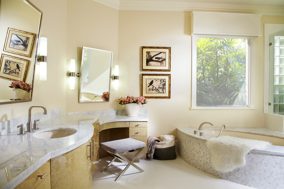 Large trendy master white tile and mosaic tile porcelain floor bathroom photo in Miami with flat-panel cabinets, light wood cabinets, an undermount tub, beige walls, an undermount sink and marble countertops