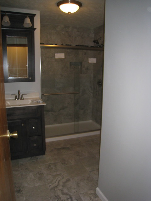 Example of a mid-sized trendy 3/4 porcelain floor bathroom design in Other with gray cabinets, a two-piece toilet, gray walls, an integrated sink and solid surface countertops