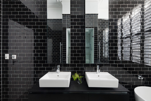 black subway tile bathroom with basins with overflow holes