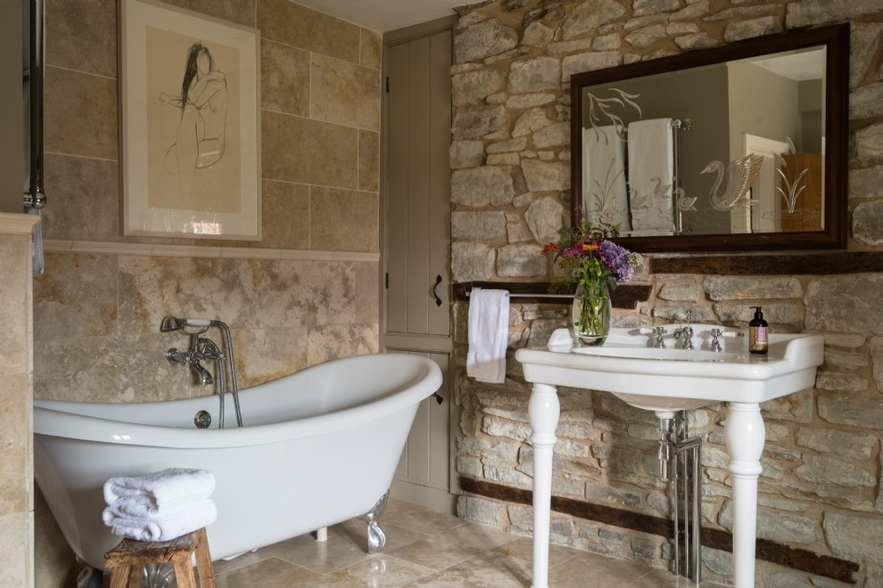 Example of a small french country 3/4 stone slab and beige tile beige floor claw-foot bathtub design in Other with beige walls and a console sink