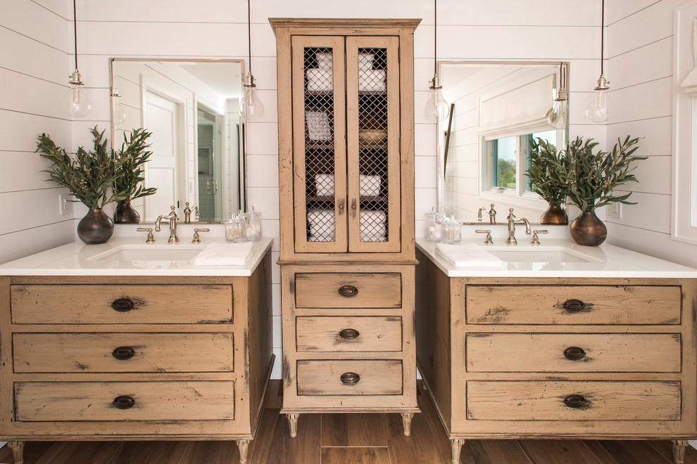 Example of a beach style master white tile brown floor bathroom design in Philadelphia with furniture-like cabinets, distressed cabinets, an undermount sink, white walls and white countertops