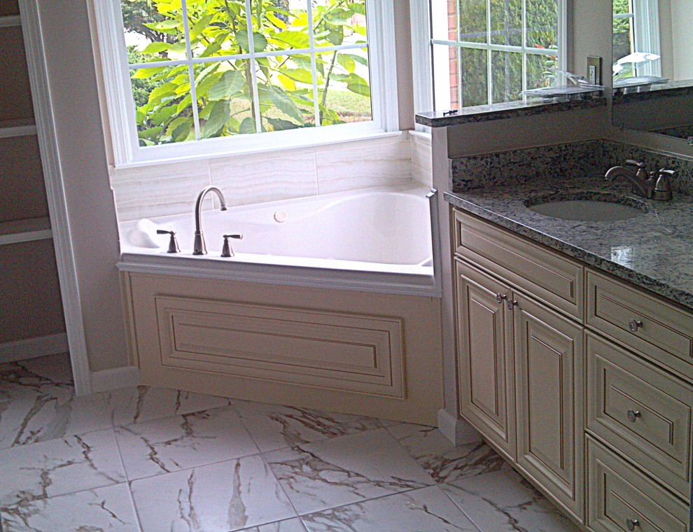 Inspiration for a large transitional master white tile and porcelain tile marble floor bathroom remodel in Atlanta with an undermount sink, raised-panel cabinets, white cabinets, granite countertops, a one-piece toilet and beige walls