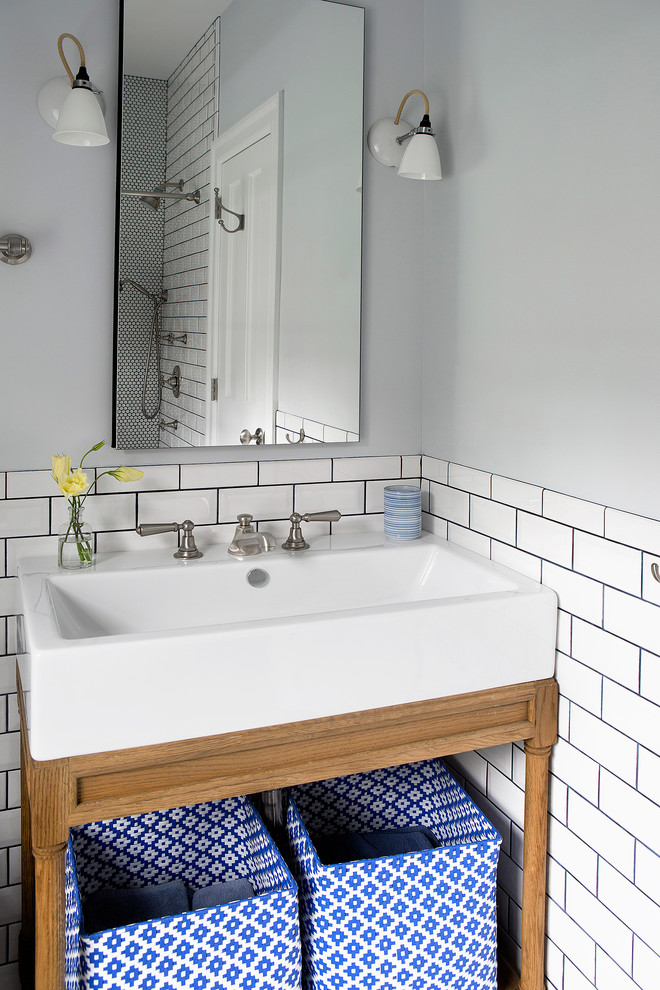 Inspiration for a small eclectic 3/4 white tile and ceramic tile bathroom remodel in New York with a console sink, furniture-like cabinets, medium tone wood cabinets, solid surface countertops, a one-piece toilet and blue walls