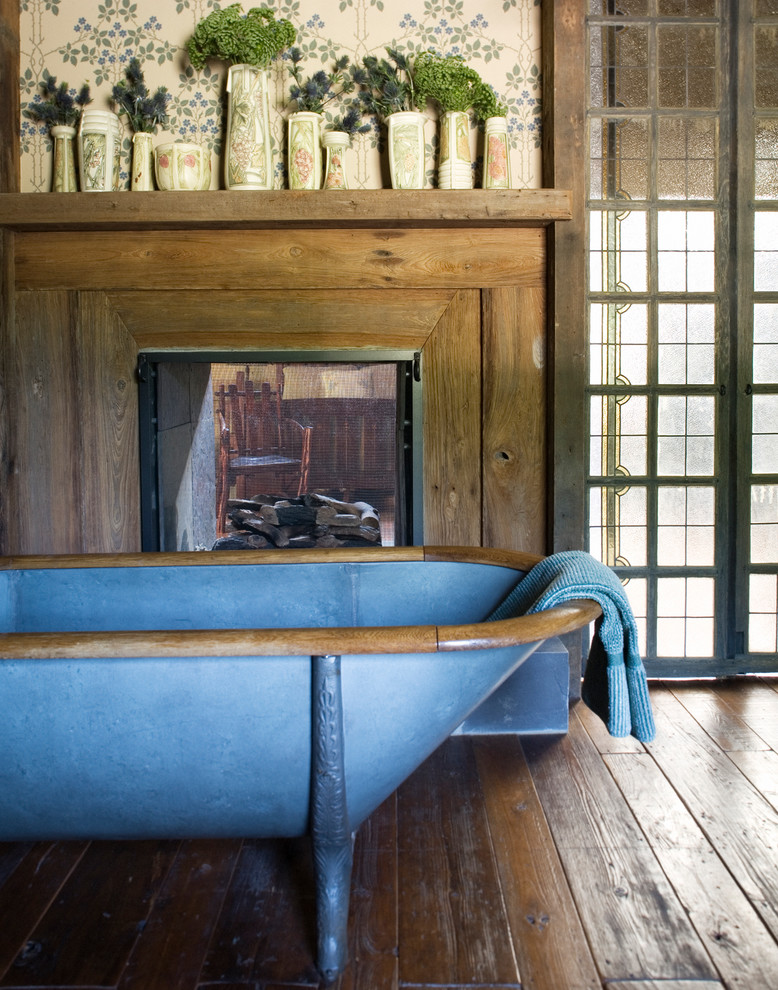 Claw-foot bathtub - rustic master dark wood floor claw-foot bathtub idea in New York