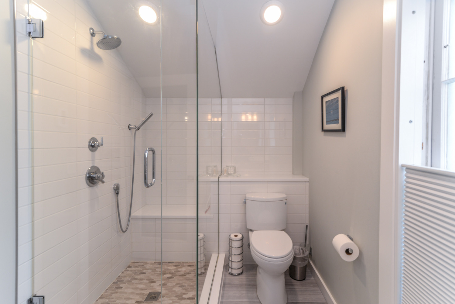 The loft bathroom packs a lot in to a smaller space. The wall tile runs the length of the bathroom to create a larger appearance, plumbing is hidden in a shelf/ledge created with a waterfall edge of q