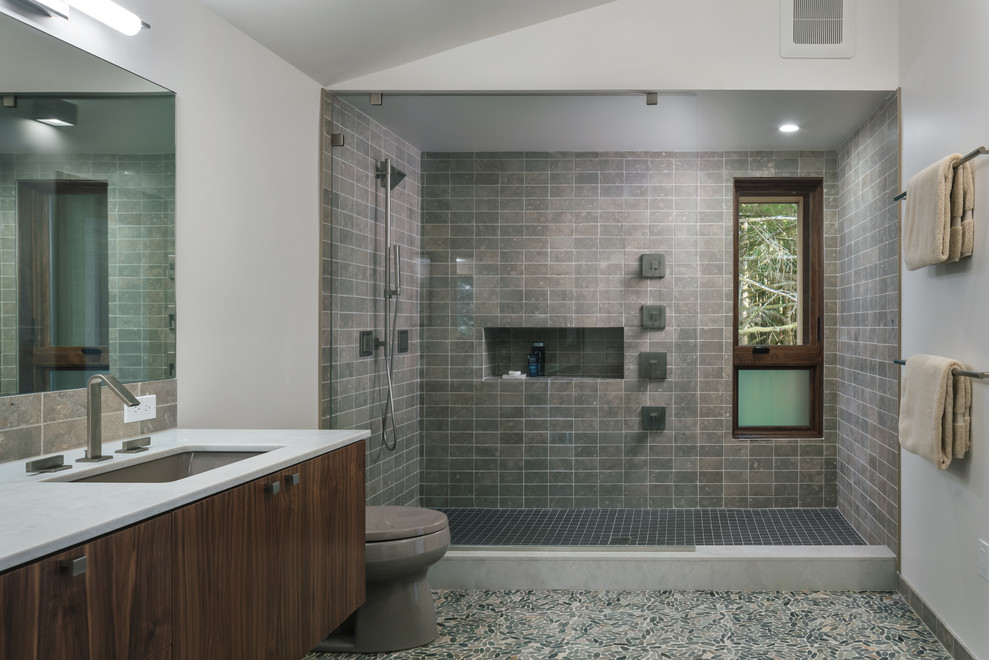 Inspiration for a contemporary master gray tile pebble tile floor and multicolored floor bathroom remodel in Portland with flat-panel cabinets, medium tone wood cabinets, white walls, an undermount sink and white countertops