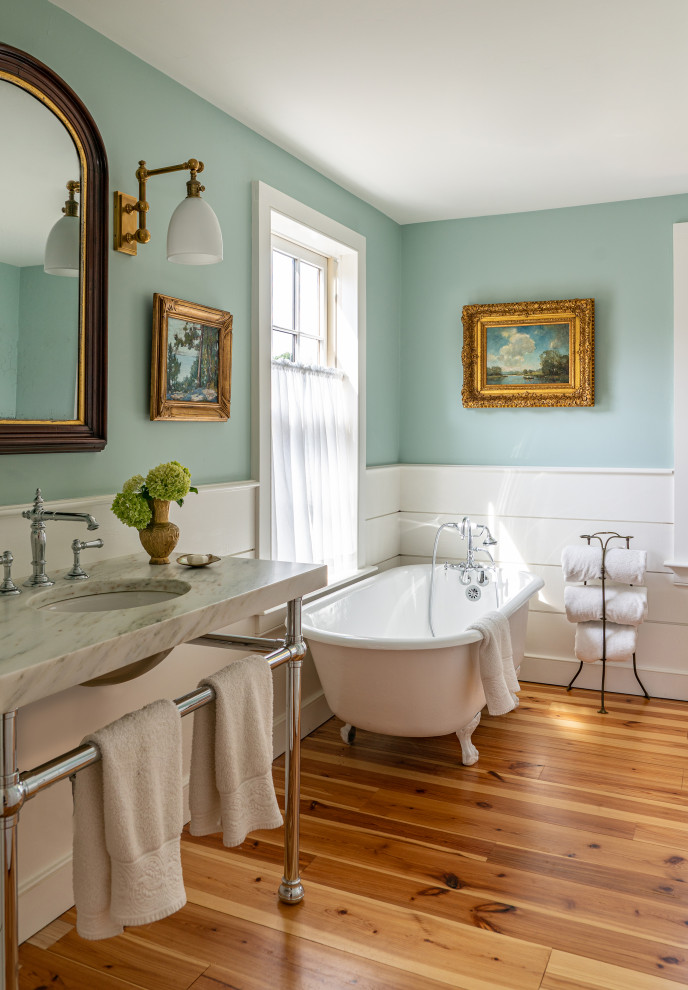 Mid-sized farmhouse white tile and ceramic tile light wood floor, single-sink and shiplap wall claw-foot bathtub photo in Boston with blue walls, a console sink, a freestanding vanity, marble countertops and white countertops