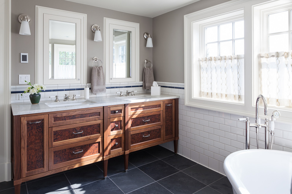 Example of a white tile and subway tile black floor and slate floor bathroom design in Seattle with furniture-like cabinets, dark wood cabinets, gray walls, an undermount sink and a hinged shower door