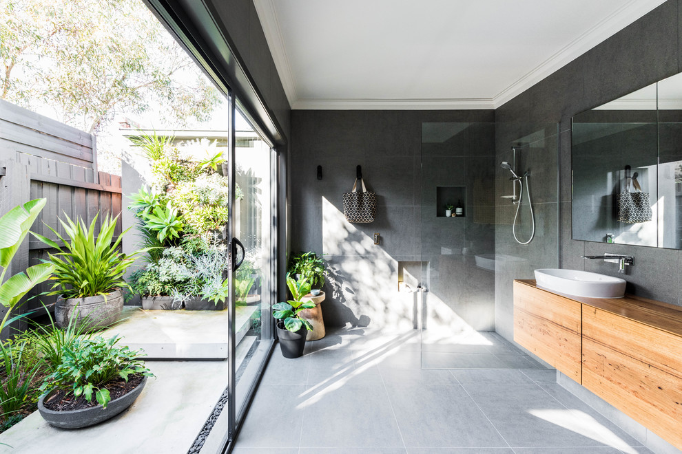 This is an example of a large contemporary master bathroom in Melbourne with flat-panel cabinets, brown cabinets, a curbless shower, gray tile, grey walls, a vessel sink, wood benchtops, grey floor, an open shower and brown benchtops.