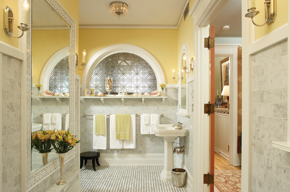 Example of a classic master gray tile and stone tile marble floor bathroom design in Minneapolis with a pedestal sink and yellow walls