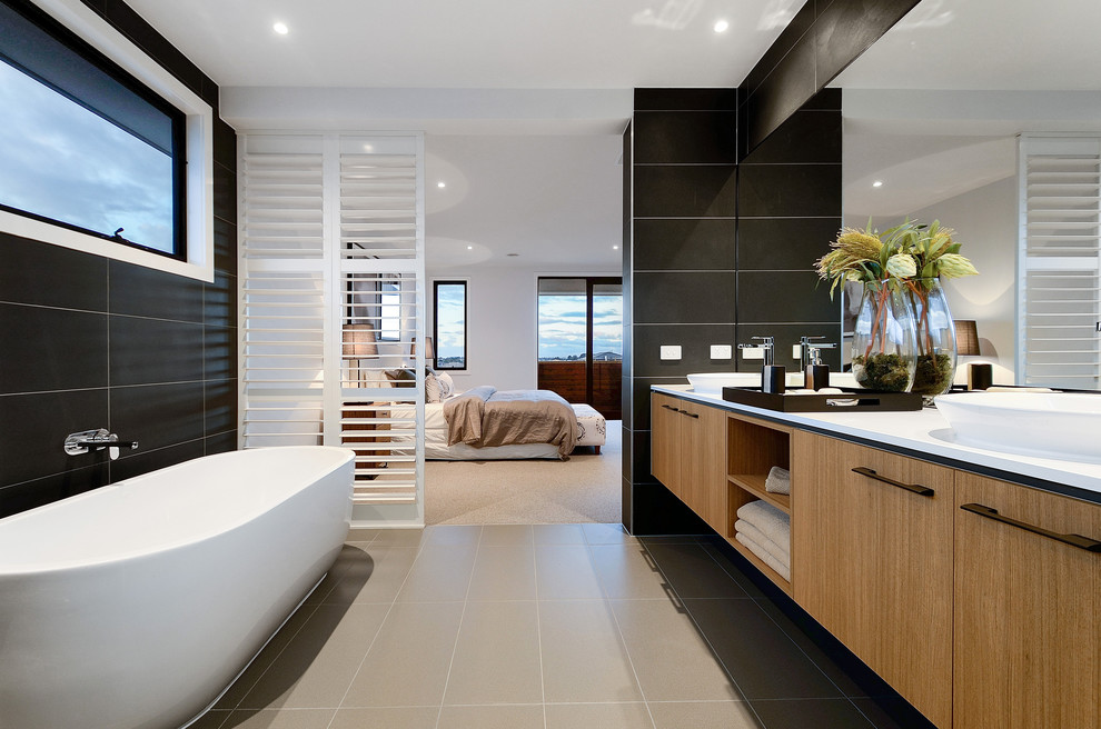 Freestanding bathtub - contemporary master black tile freestanding bathtub idea in Melbourne with flat-panel cabinets, light wood cabinets, black walls and a vessel sink