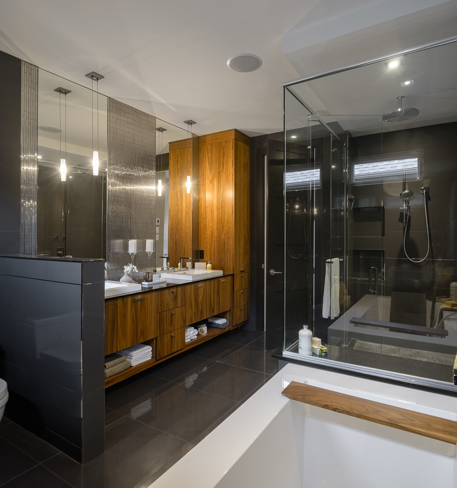 Example of a large trendy master black tile and porcelain tile bathroom design in Ottawa with flat-panel cabinets, medium tone wood cabinets, a one-piece toilet and black walls