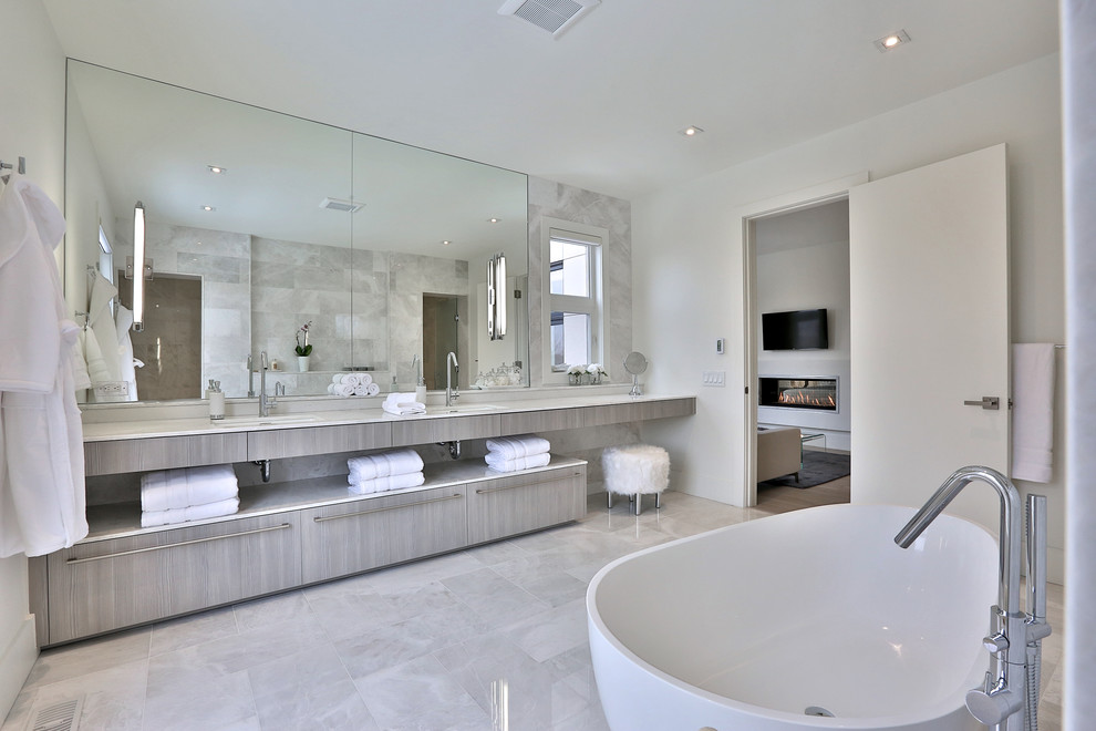 Freestanding bathtub - huge contemporary master gray tile and stone tile marble floor freestanding bathtub idea in Toronto with flat-panel cabinets, light wood cabinets, white walls, an undermount sink and marble countertops