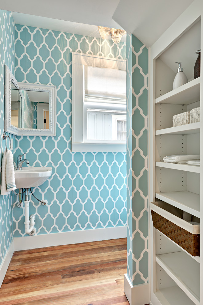 Example of a small transitional medium tone wood floor bathroom design in Austin with a wall-mount sink, blue walls and open cabinets