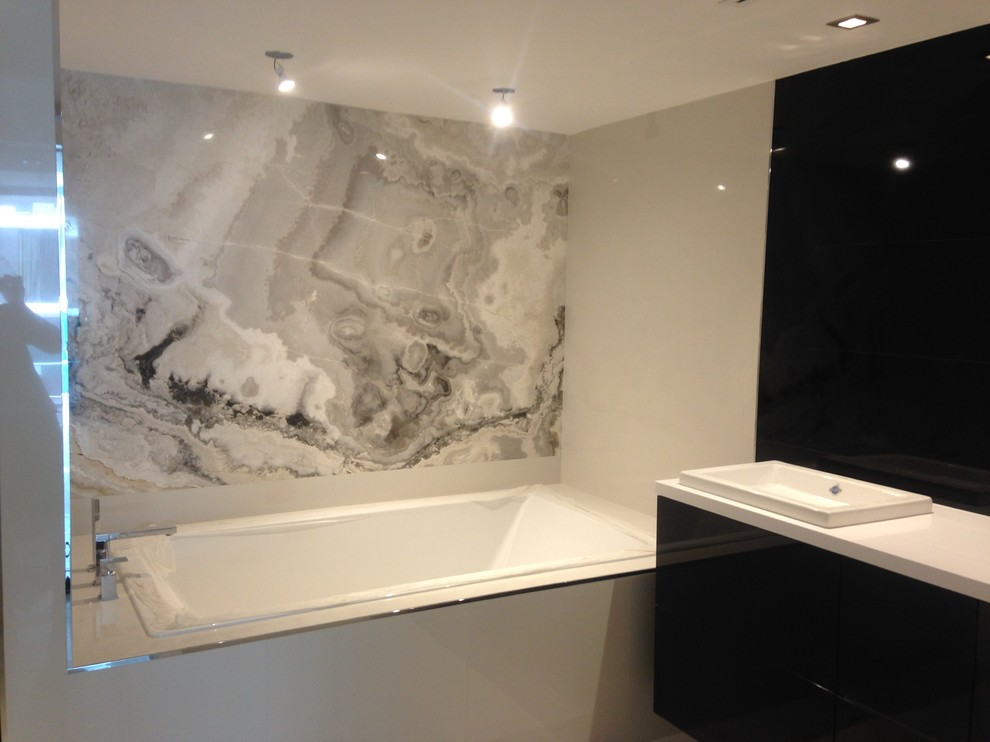 Example of a trendy gray tile bathroom design in Miami with onyx countertops