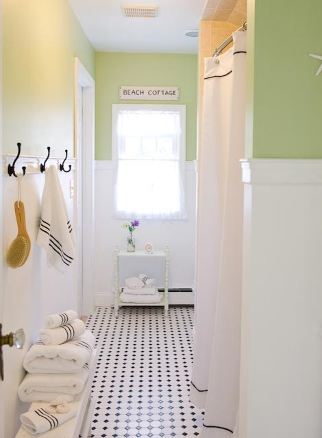 Example of a coastal black and white tile bathroom design in New York