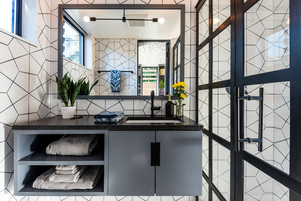 Example of a small trendy 3/4 white tile and ceramic tile alcove shower design in Seattle with flat-panel cabinets, an undermount sink, solid surface countertops, a hinged shower door, black countertops and gray cabinets
