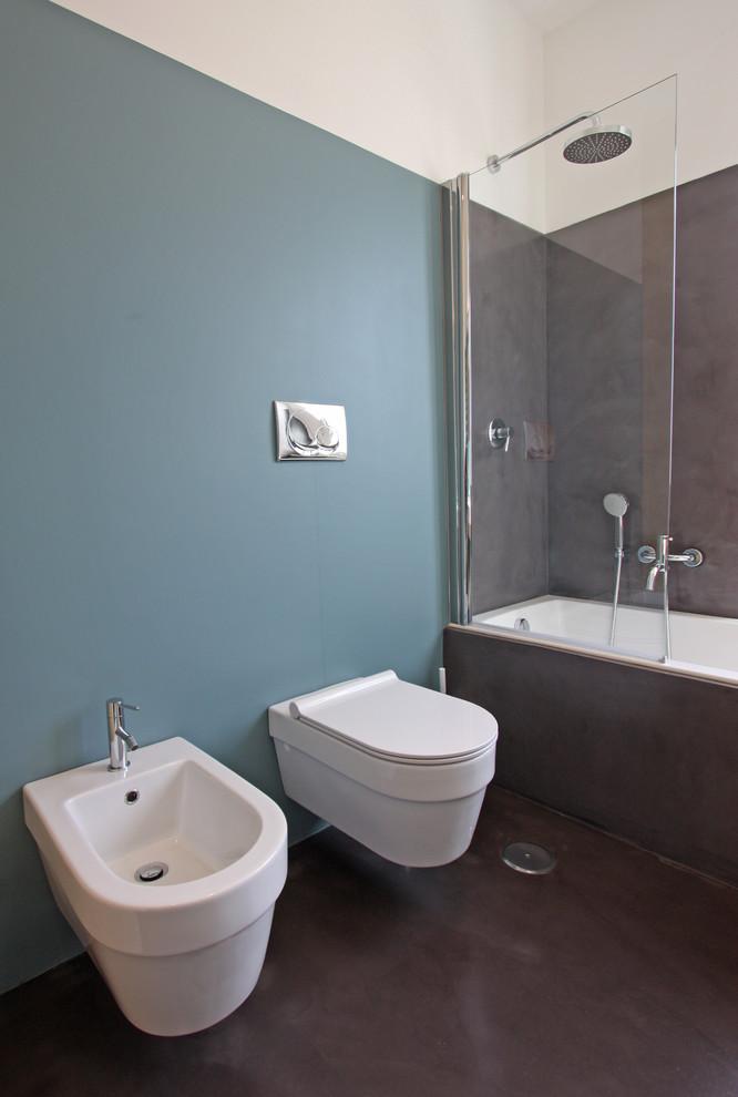 Immagine di una stanza da bagno minimal con vasca da incasso, vasca/doccia, WC sospeso e pareti blu