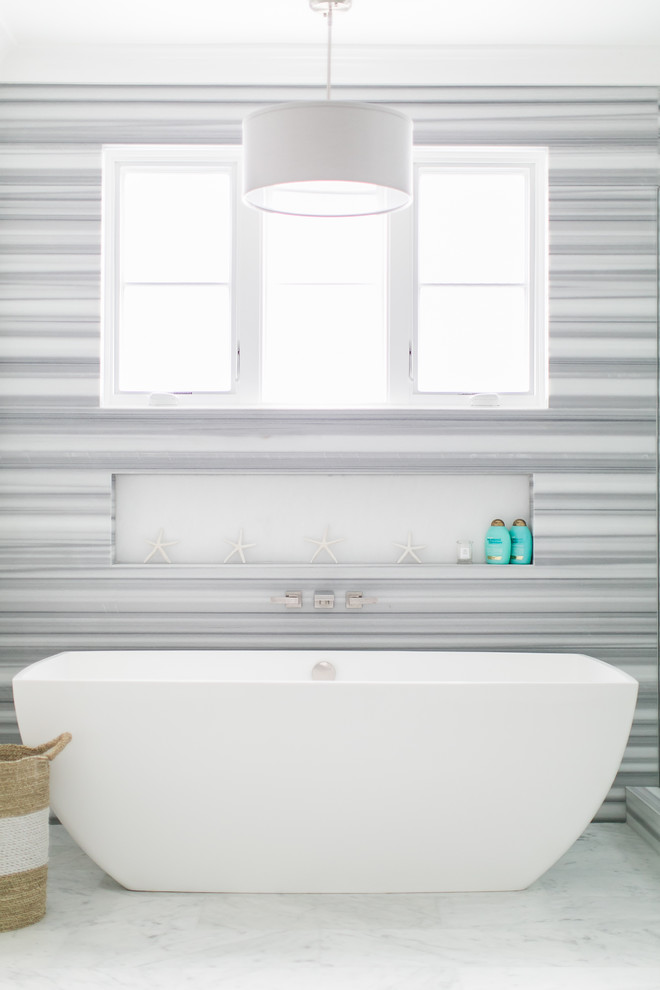 Inspiration for a mid-sized coastal master white tile and ceramic tile marble floor bathroom remodel in Orange County with flat-panel cabinets, white cabinets, a one-piece toilet, white walls, an undermount sink and quartz countertops