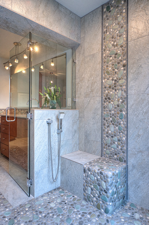 This stone backsplash harmoniously blends with the smooth tiles.