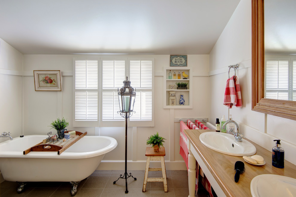 Example of an eclectic claw-foot bathtub design in Brisbane with a drop-in sink, wood countertops and white walls