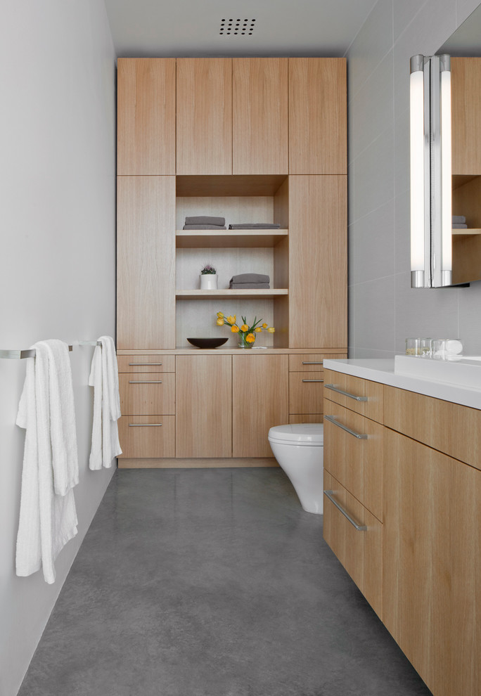 Bathroom - small contemporary porcelain tile and gray tile concrete floor bathroom idea in Phoenix with flat-panel cabinets, light wood cabinets, white walls, solid surface countertops and a drop-in sink