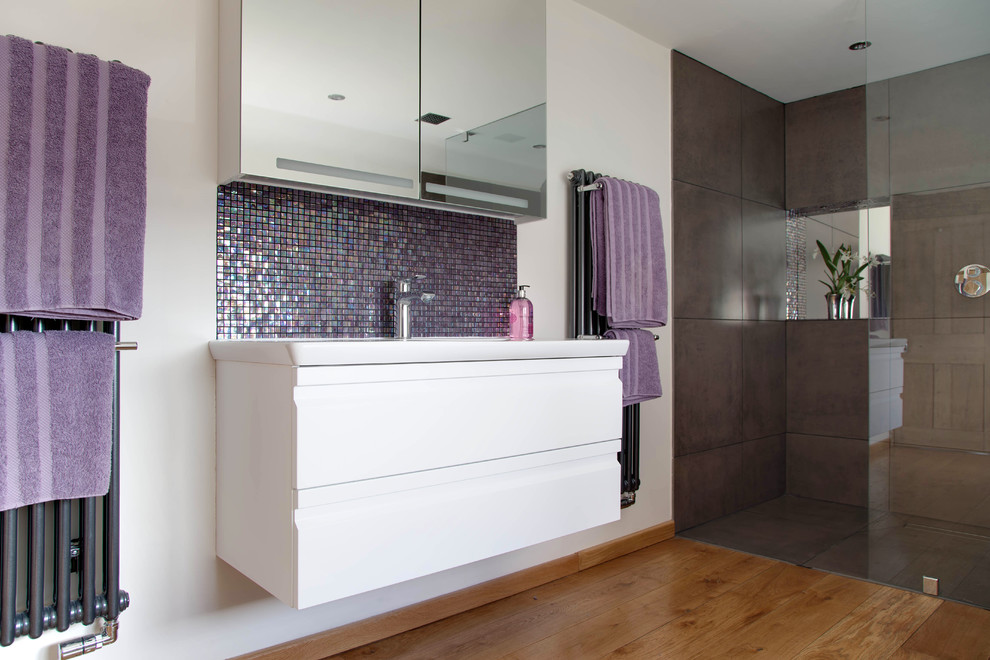 This is an example of a large contemporary bathroom in Other with flat-panel cabinets, white cabinets, an alcove shower, multi-coloured tiles, mosaic tiles, white walls and medium hardwood flooring.