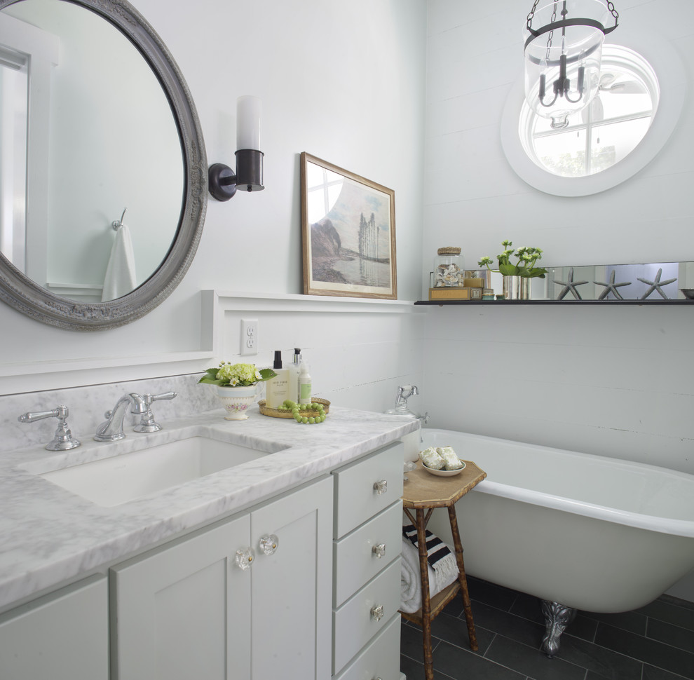 Inspiration for a mid-sized coastal master porcelain tile and black floor claw-foot bathtub remodel in Atlanta with marble countertops, shaker cabinets, white cabinets, white walls, an undermount sink and white countertops