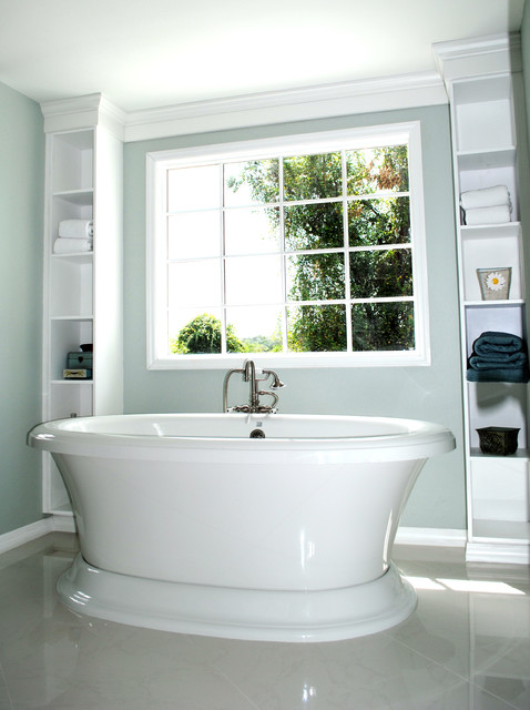 Bath featuring freestanding tub framed by built-in shelves ...