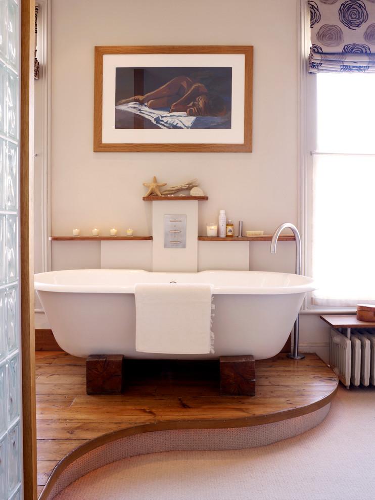 Example of a mid-sized trendy master medium tone wood floor freestanding bathtub design in London with beige walls