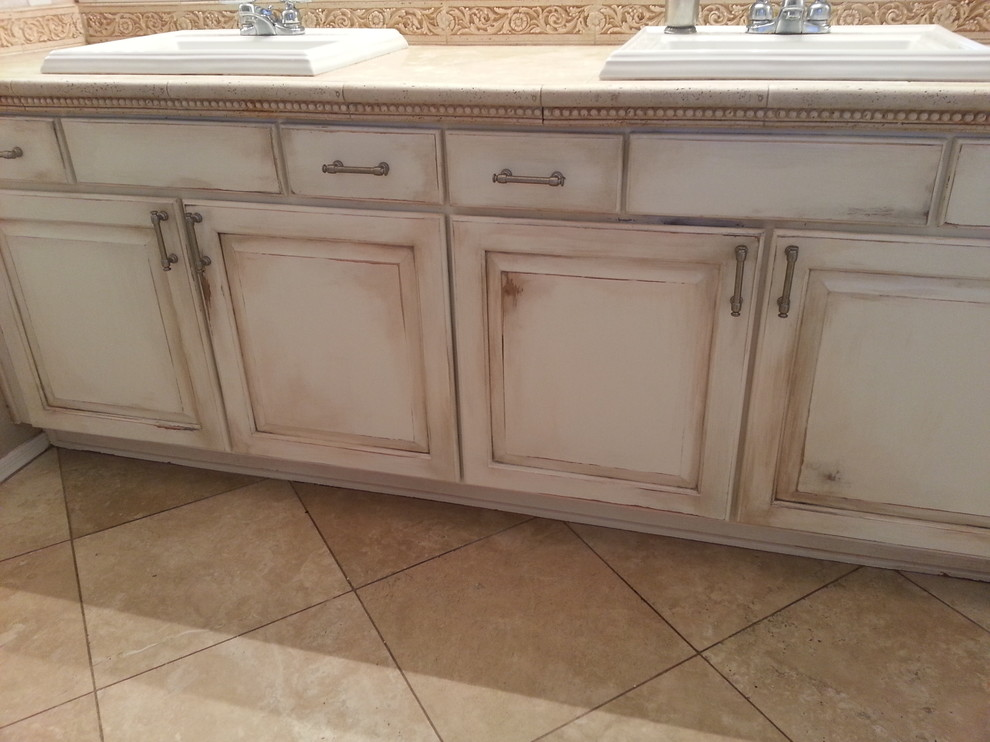 Mid-sized mountain style master beige tile and stone tile travertine floor bathroom photo in Phoenix with a drop-in sink, raised-panel cabinets, distressed cabinets, limestone countertops, a one-piece toilet and multicolored walls