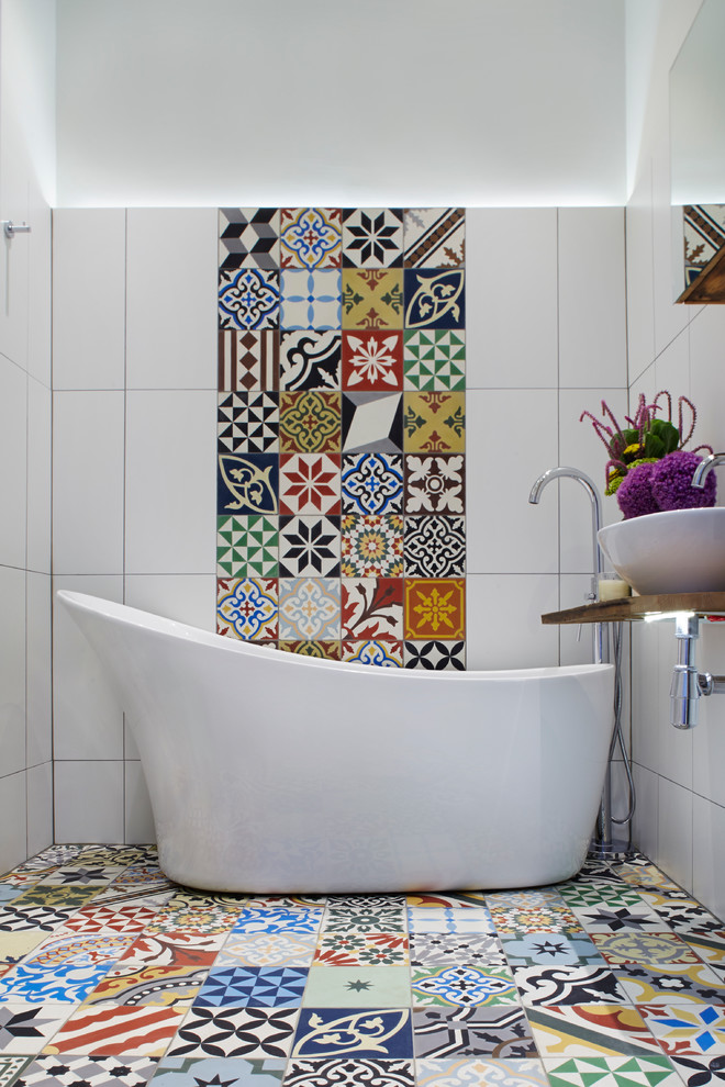 Inspiration for a mediterranean master multicolored tile and stone tile multicolored floor freestanding bathtub remodel in London with a vessel sink, wood countertops, multicolored walls and brown countertops