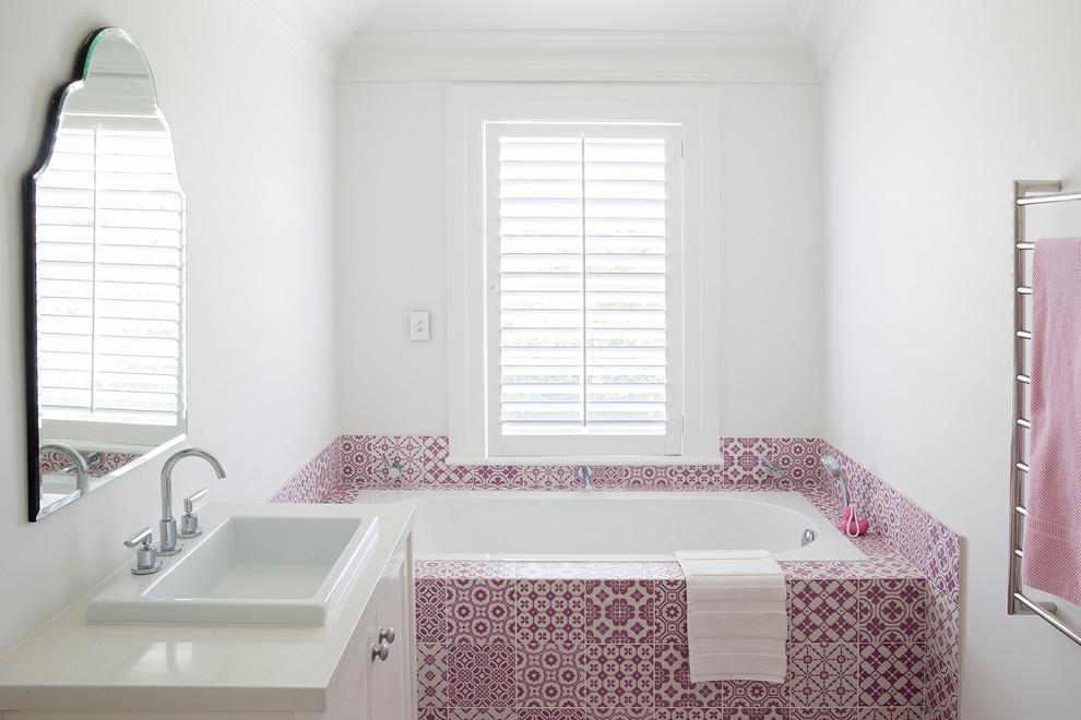 Новые идеи обустройства дома: главная ванная комната среднего размера в средиземноморском стиле с накладной раковиной, белыми фасадами, ванной в нише, белыми стенами и розовой плиткой