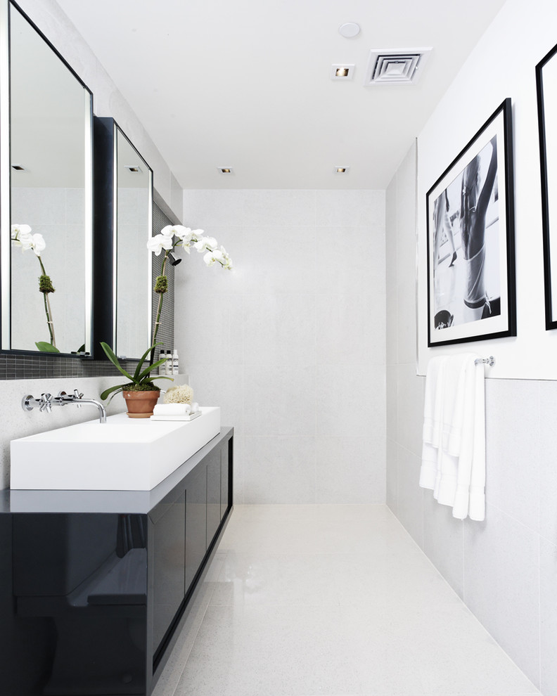 Trendy white floor bathroom photo in New York with a vessel sink and black cabinets