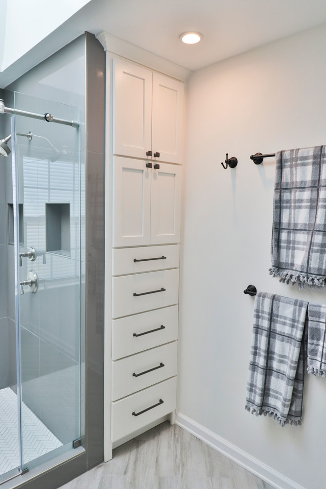 Alcove shower - mid-sized transitional 3/4 vinyl floor and gray floor alcove shower idea in DC Metro with shaker cabinets, white cabinets, gray walls, an undermount sink, marble countertops, a hinged shower door and white countertops