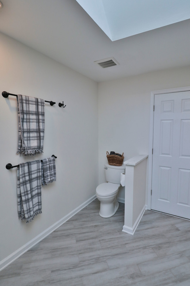 Example of a mid-sized transitional 3/4 vinyl floor and gray floor alcove shower design in DC Metro with shaker cabinets, white cabinets, gray walls, an undermount sink, marble countertops, a hinged shower door and white countertops