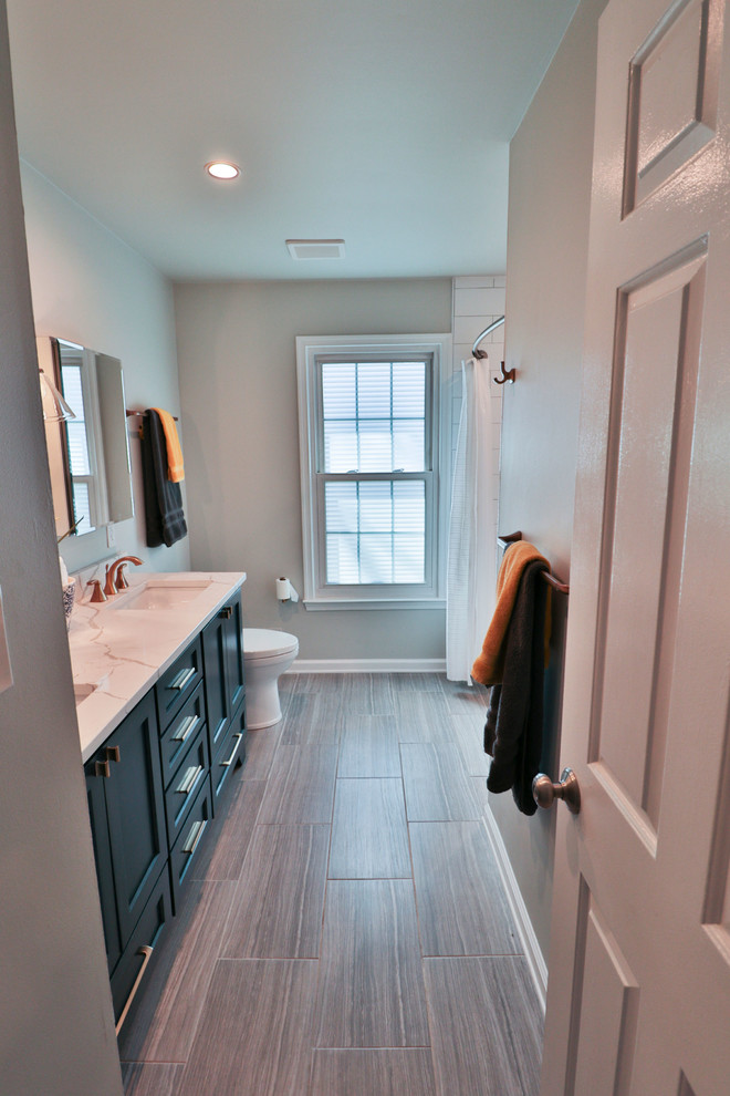 Inspiration for a mid-sized transitional 3/4 white tile and subway tile porcelain tile and brown floor bathroom remodel in DC Metro with recessed-panel cabinets, blue cabinets, gray walls, an undermount sink, marble countertops and white countertops