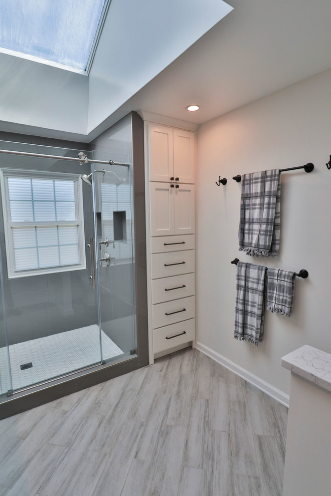 Inspiration for a mid-sized transitional 3/4 vinyl floor and gray floor alcove shower remodel in DC Metro with shaker cabinets, white cabinets, gray walls, an undermount sink, marble countertops, a hinged shower door and white countertops