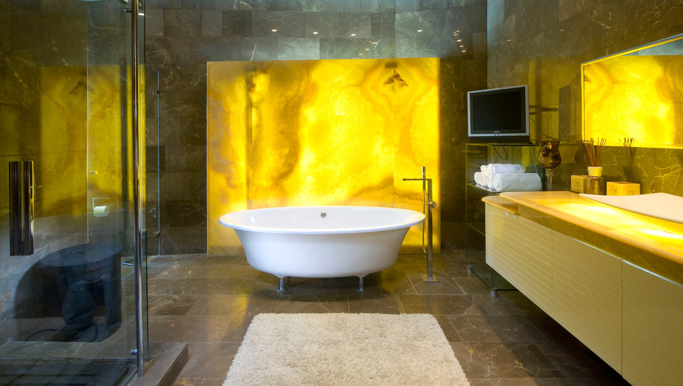 Example of a trendy stone slab claw-foot bathtub design in Other with onyx countertops