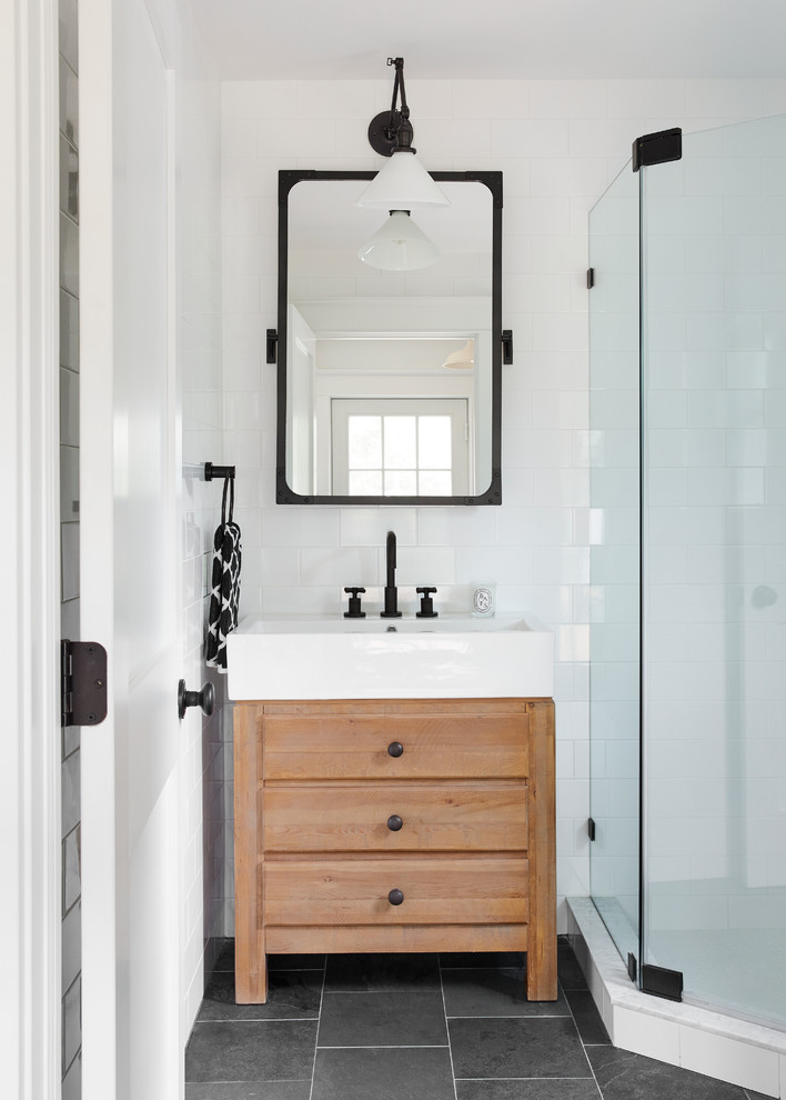 Inspiration for a small country white tile and ceramic tile corner shower remodel in New York with flat-panel cabinets, medium tone wood cabinets, white walls, a console sink and a hinged shower door