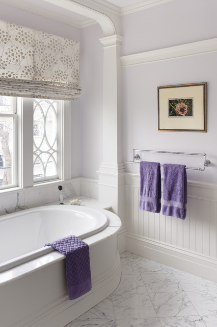 Elegant master white tile drop-in bathtub photo in Boston with white cabinets, marble countertops and purple walls