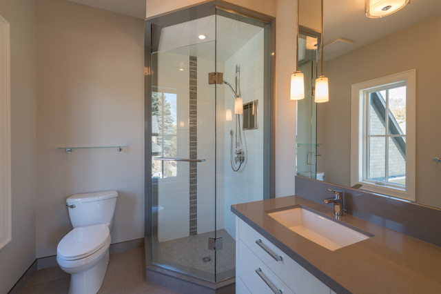 Example of a trendy kids' gray tile and porcelain tile porcelain floor corner shower design in Toronto with an undermount sink, flat-panel cabinets, white cabinets, solid surface countertops, a two-piece toilet and gray walls