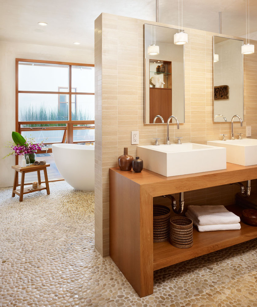 Inspiration for a mid-sized tropical master pebble tile and beige tile pebble tile floor and multicolored floor bathroom remodel in Los Angeles with a vessel sink, open cabinets, dark wood cabinets, a wall-mount toilet, beige walls, wood countertops and brown countertops