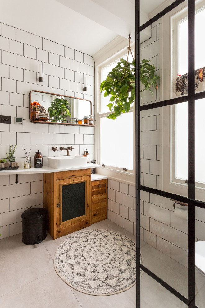 Inspiration for a transitional white tile gray floor bathroom remodel in Sussex with recessed-panel cabinets, medium tone wood cabinets, a vessel sink and white countertops