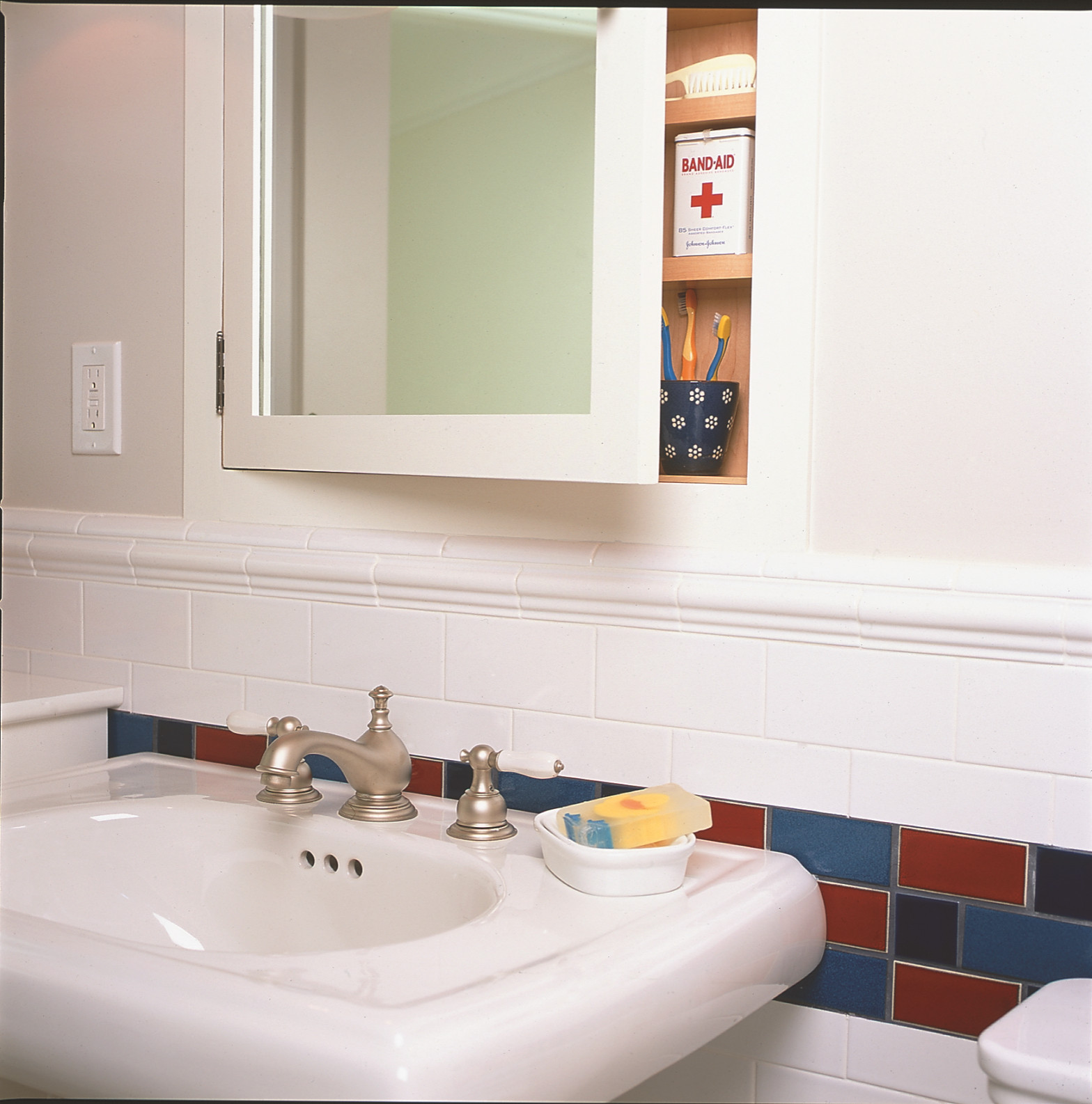Bathroom with red blue and white tile and pedestal sink