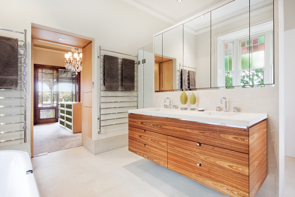 Bathroom - large contemporary master white tile and stone tile limestone floor bathroom idea in Sydney with an integrated sink, flat-panel cabinets, medium tone wood cabinets, white walls and a wall-mount toilet