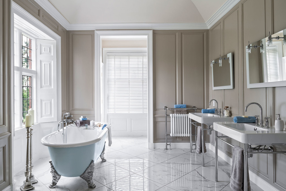 Large elegant master white tile marble floor claw-foot bathtub photo in Hampshire with brown walls, a console sink and open cabinets