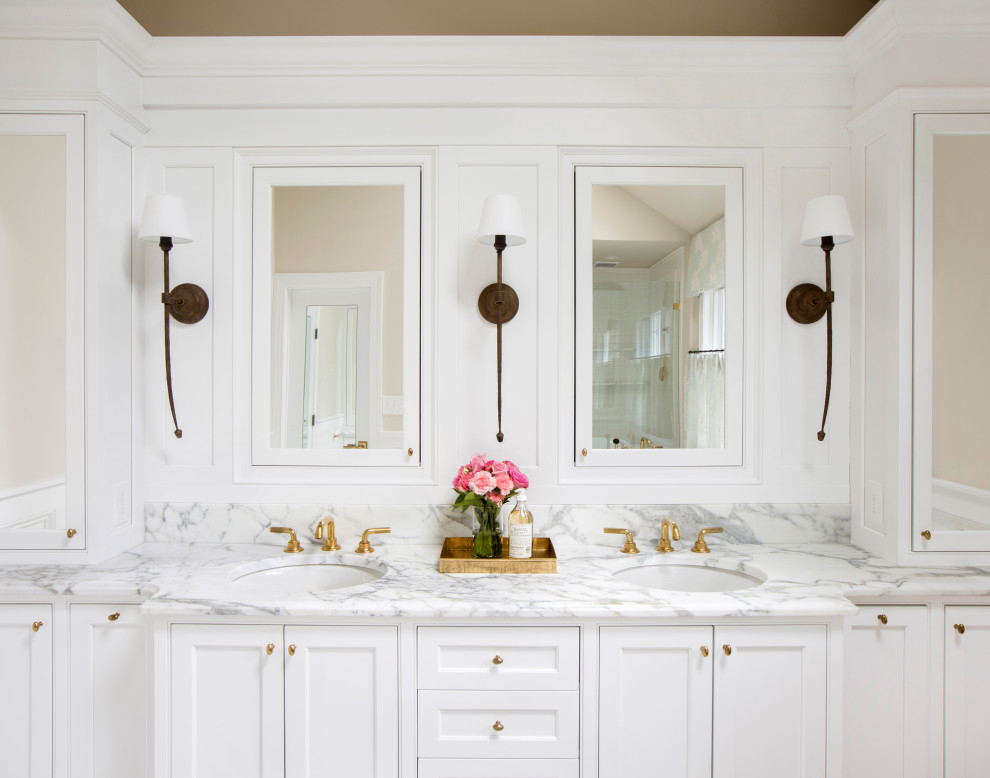 Inspiration for a large timeless master white tile and ceramic tile marble floor, beige floor, double-sink, vaulted ceiling and wainscoting bathroom remodel in Philadelphia with recessed-panel cabinets, white cabinets, a two-piece toilet, beige walls, an undermount sink, marble countertops, a hinged shower door, white countertops and a built-in vanity