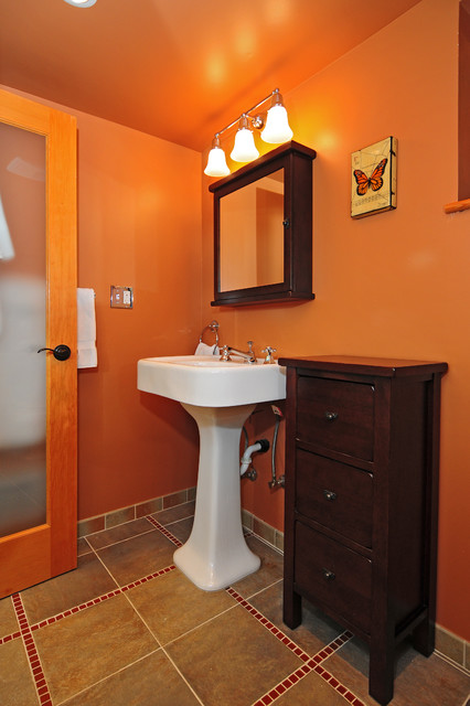 Arts and crafts 3/4 multicolored tile and ceramic tile porcelain floor bathroom photo in Seattle with a pedestal sink, furniture-like cabinets, dark wood cabinets, a two-piece toilet and orange walls